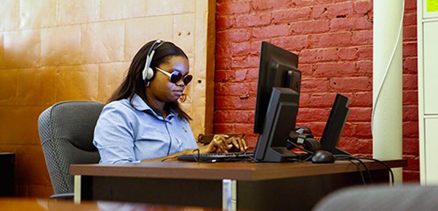 #pracegover Mulher negra está sentada no escritório usando fones e óculos escuros e mexendo no computador