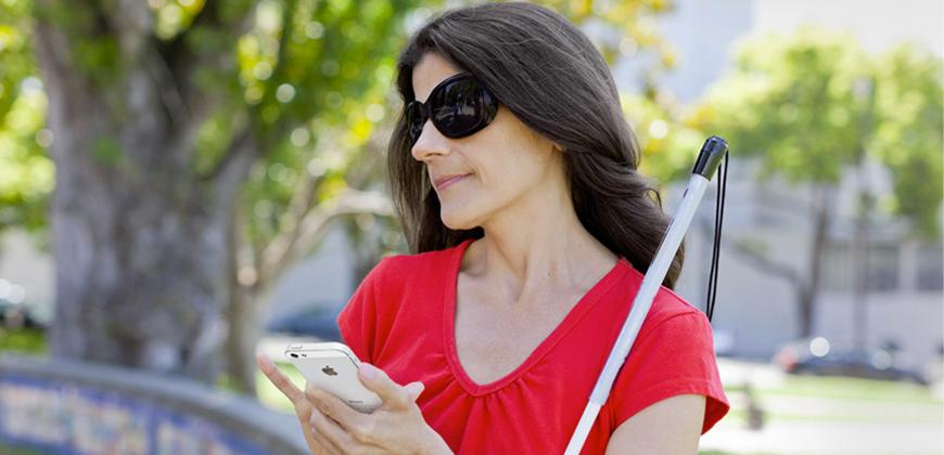 #pracegover Mulher com cabelos longos e escuros está usando óculos escuros e uma blusa vermelha segurando um celular e uma bengala.