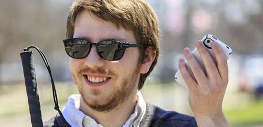 #pracegover Homem ruivo de óculos escuros, está sorrindo e segurando um celular e uma bengala